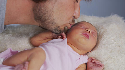 Proud father cuddles his baby girl as they stare at each other. Dad rubs noses Live Action