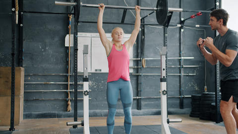 Pretty girl lifting weight in gym while man trainer motivating student talking Live Action