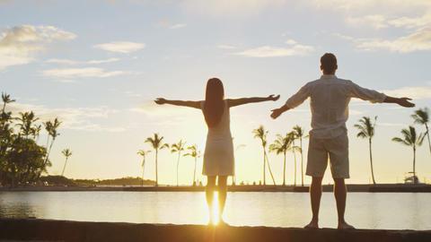 Serene happy couple enjoying nature sunset raising arms to sky enjoying freedom Live Action