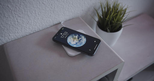 Smartphone being placed on wireless charging pad to charge battery Live Action
