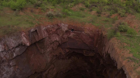 Drone is flying on high speed over a man sitting on the slackline, huge quarry Live Action
