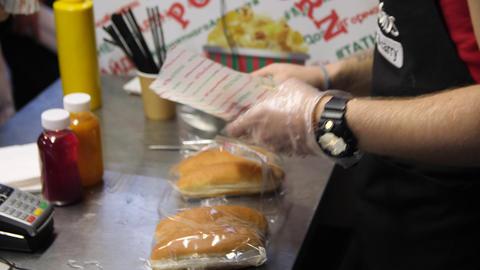 man puts tasty sausage into fresh bun cooking hotdog in cafe Live Action