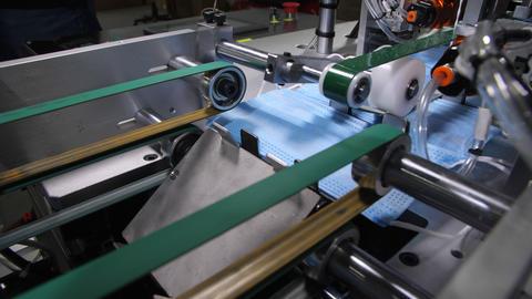 production line transports finished surgical masks in shop Live Action