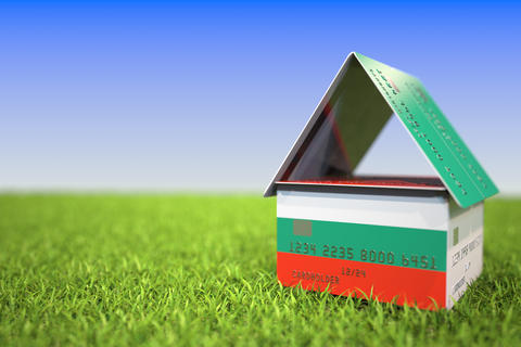 Flag of Bulgaria on plastic bank card house in the grass. Mortgage related 3D Photo