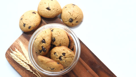 Jar full of chocolate chip cookies on white background Live Action
