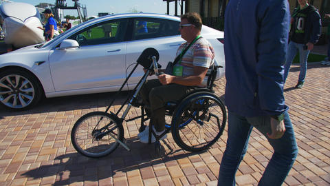 man in wheelchair rides past car and Skyway transport Live Action