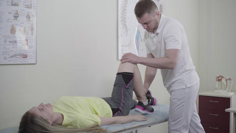 Young confident Caucasian physician examining female patient lying on medical Live Action