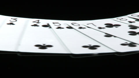 A deck of cards laid out rotates in front of a camera Footage