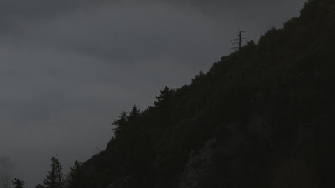 Time-lapse of clouds and sun rising up a forested... Stock Video Footage