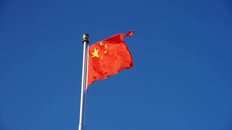 Chinese red flag flutters in wind & blue sky Footage