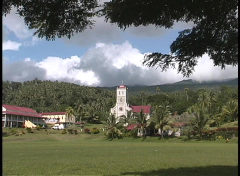 A small village sitting near the hills and trees of an island in the South Pacific Footage