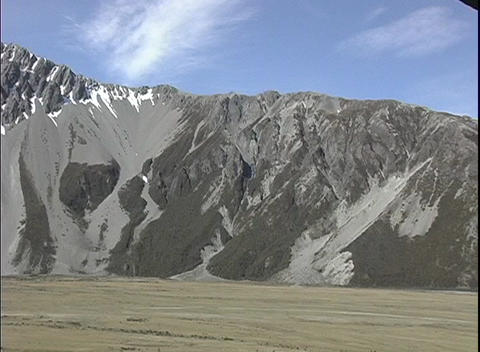 Camera pans the Southern Alps in New Zealand with a grass... Stock Video Footage