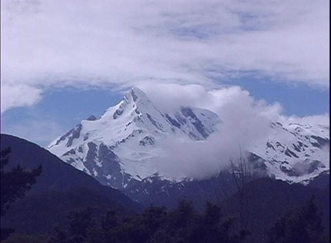 An establishing-shot of clouds hiding majestic snow- covered mountain peak in New Zealand Footage