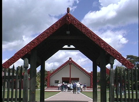 View from an archway of people walking toward a building in a Maori village Footage