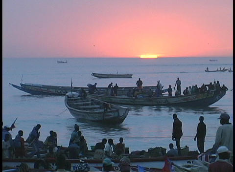 People wait and watch on shore as fishing boats come in at golden-hour near Senegal, West Africa Footage