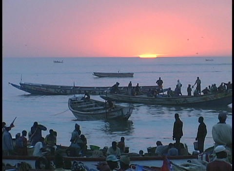 People wait and watch on shore as fishing boats come in... Stock Video Footage
