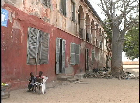 Children play outside an old former slave house in West Africa Footage