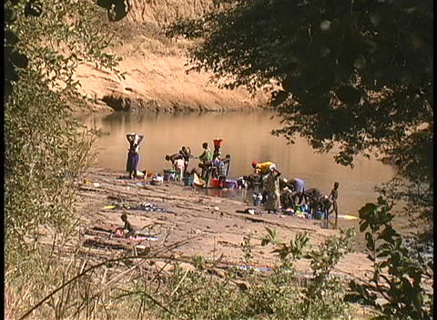 Women wash clothes in the Niger River in West Africa Stock Video Footage