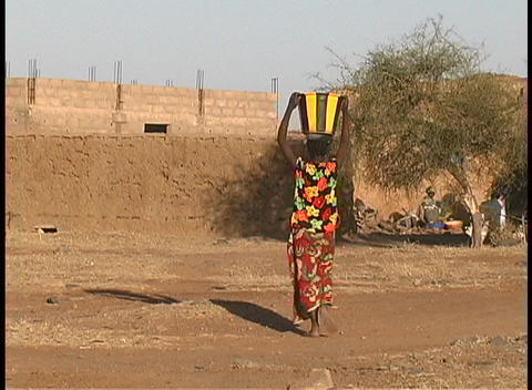 A woman carries a basket with water on her head as she walks through a village in Mali, West Africa Footage