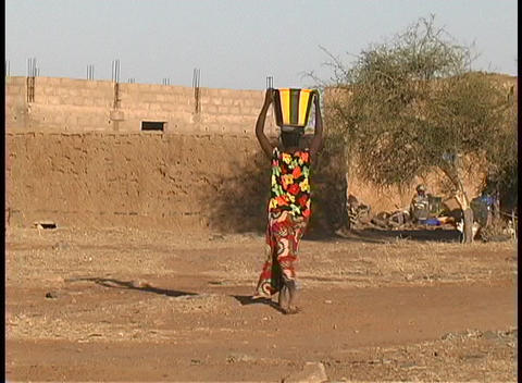 A woman carries a basket with water on her head as she... Stock Video Footage