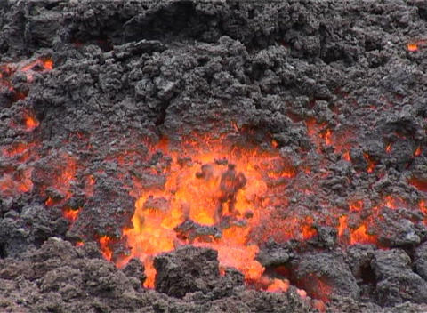 Lava flows from a volcano beneath a covering of ash Stock Video Footage
