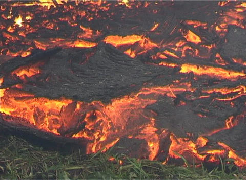 Molten lava flows beneath a black crust Footage