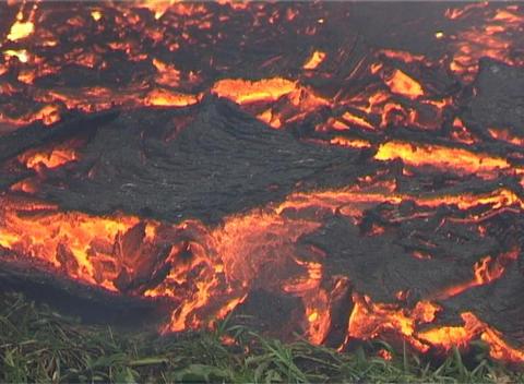 Molten lava flows beneath a black crust Stock Video Footage