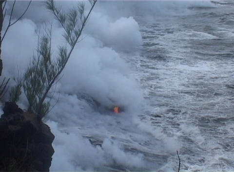 Clouds of steam rise from a lava flow as ocean waves roll in Footage