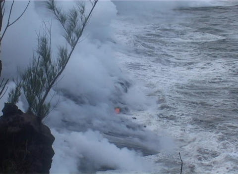 Clouds of steam rise from a lava flow as ocean waves roll in Stock Video Footage
