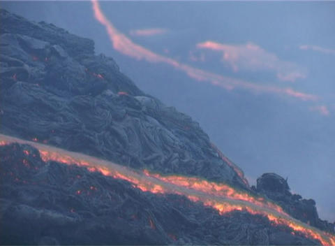 Rivers of red hot lava flow down the side of a volcano Footage