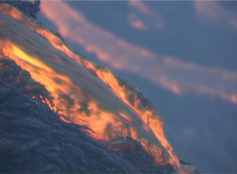 Red hot lava flows over the rim of a volcanic cone during... Stock Video Footage