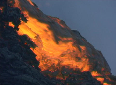 Red hot lava flows over the rim of a volcanic cone during an eruption Footage