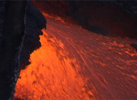 Red hot lava flows down the slopes of a volcano Footage