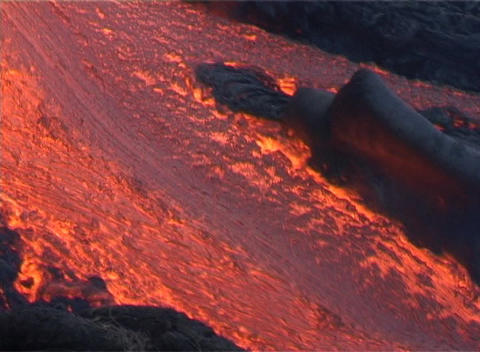 Red hot lava flows down a volcano past blackened trees... Stock Video Footage
