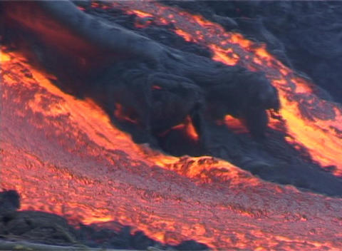 Red hot lava flows down a volcano past blackened trees and scorched plants Footage