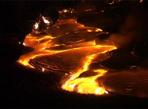 Hot molten lava slowly flows down a mountainside, through... Stock Video Footage