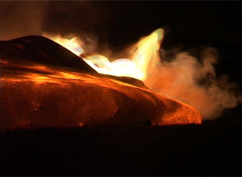 Flames erupt around a lava flow during a volcanic eruption Stock Video Footage