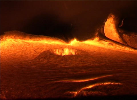 Molten lava oozes from a volcano, erupting eerily into domes belching flames Footage