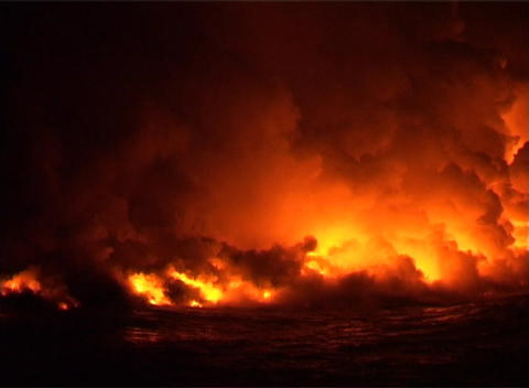 Clouds of flame, smoke, and steam billow into the night sky when lava flows into the ocean Footage