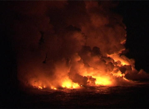 Clouds of smoke and steam billow into the night sky when molten lava flows into the ocean Footage