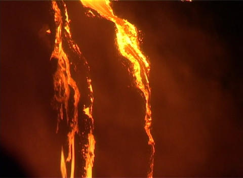 A waterfall of molten lava trickles down a steep slope... Stock Video Footage