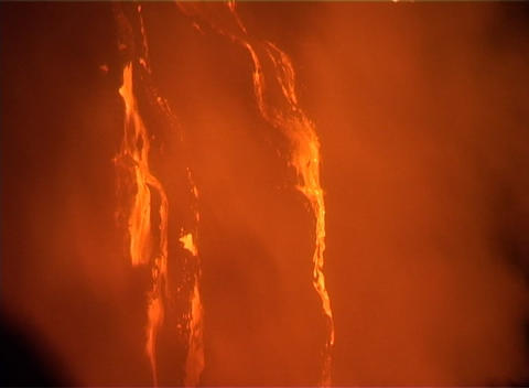 A waterfall of molten lava trickles down a steep slope during a volcanic eruption Footage