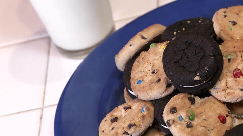A plate full of cookies with a glass of milk Footage