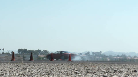 low shot of a red car as it smokes its tires through a drifting course at Camarillo Airport in Camar Footage