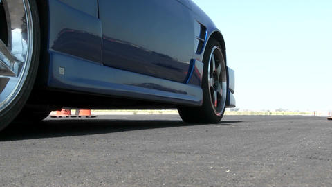A blue car revs its engine before taking off at a... Stock Video Footage
