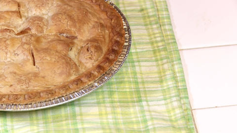 A fresh baked apple pie cools on a green kitchen towel Footage
