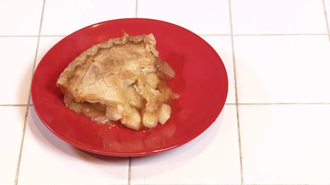 A fresh baked slice of apple pie steams on a red plate Footage