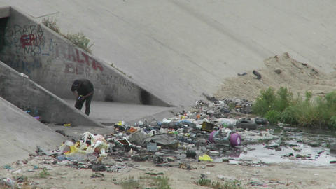 A man walks amongst garbage and litter in a drainage ditch Stock Video Footage