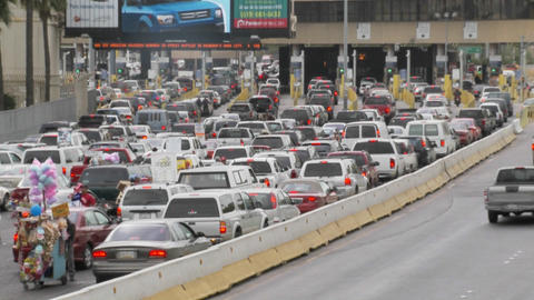 Cars wait at the US Mexico border to cross back into the... Stock Video Footage