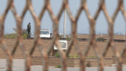 A border patrol agent is viewed through the border fence... Stock Video Footage